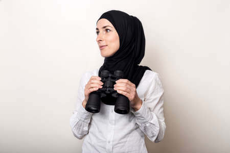 Friendly young Muslim woman in white shirt and hijab holds binoculars with a smile. Banner.