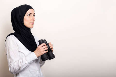 Friendly young Muslim woman in white shirt and hijab holds binoculars. Banner.