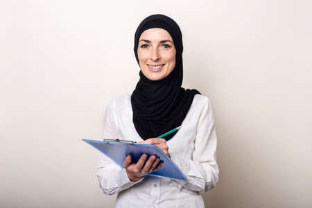 Friendly young Muslim woman in a white shirt and hijab holds a clipboard with a smile. Banner. Фото со стока