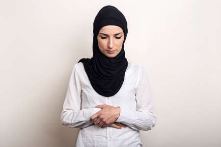 Young Muslim woman dressed in a white shirt and hijab praying on a light background. Banner. Фото со стока