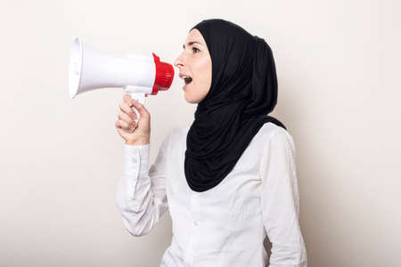Muslim young woman in hijab holds a megaphone in her hands and shouts into it on a light background. Banner.