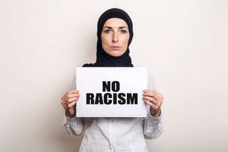 Young Muslim woman in a white shirt and hijab with a sad face holds a blank sheet of paper. Place for your text. Banner. Added Text No racism. Фото со стока