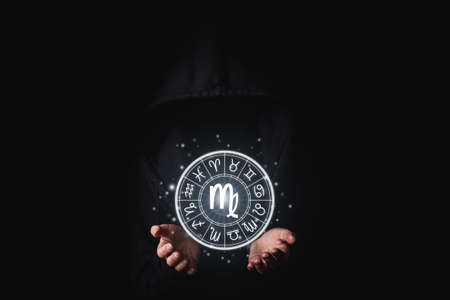 A woman in a black mantle with her palms holds the glowing astrological signs of the zodiacs on a black background.