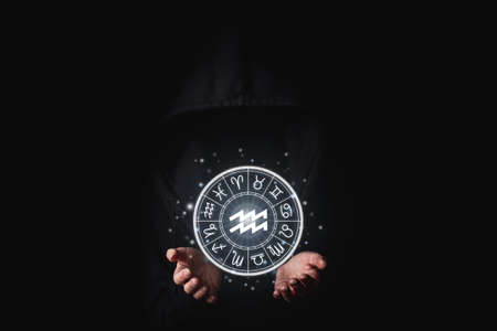 A woman in a black robe of the face is not visible with her palms holding the glowing astrological signs of the zodiacs in the dark. Фото со стока