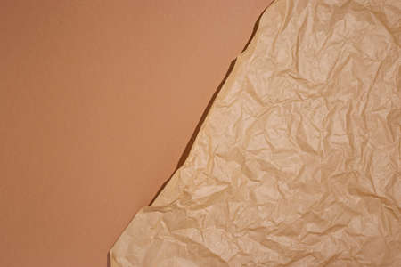 Crumpled craft paper on a brown cardboard background. Фото со стока