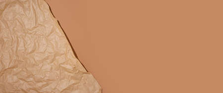 Crumpled craft paper on a brown cardboard background. Banner.