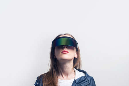Young woman in virtual reality glasses in a blue jacket looks up on a light background.