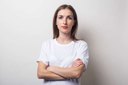 Young woman in a white T-shirt with crossed arms on a light background. Фото со стока