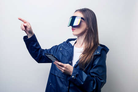 Young woman in virtual reality glasses with a phone points a finger to the side on a light background. Фото со стока