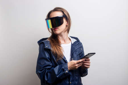 Young woman in virtual reality glasses with a phone in a blue jacket on a light background.
