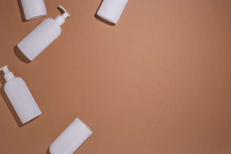 White bottles with a dispenser lie on a brown cardboard background. Top view, flat lay.