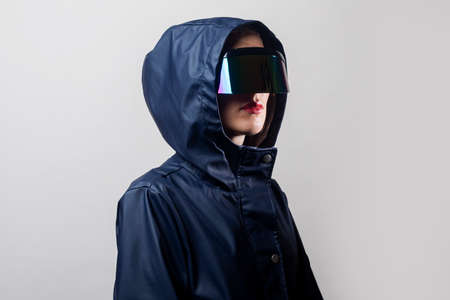 Young woman in virtual reality glasses in a blue jacket in a hood on a light background. Фото со стока