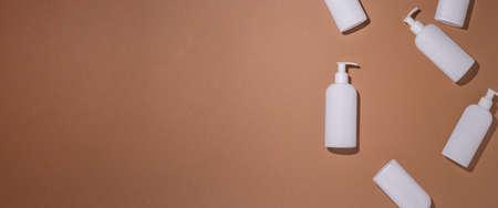 Dispenser bottles lie on a brown cardboard background. Top view, flat lay. Banner.