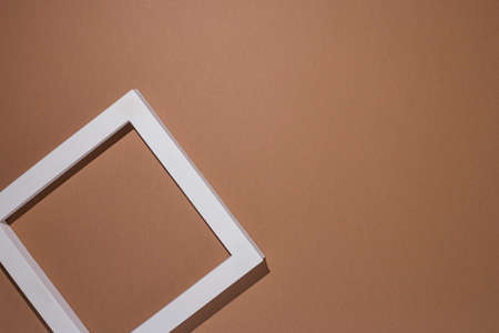 Podium for presentation square white frame on brown background. Top view, flat lay. Фото со стока