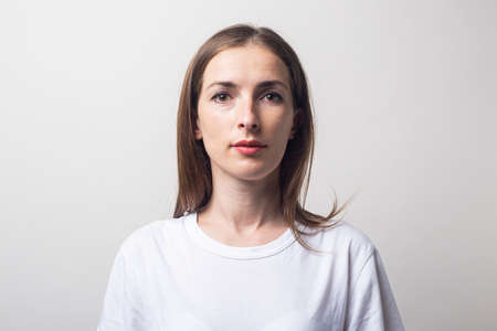 Young woman in a white T-shirt on a light background. Фото со стока