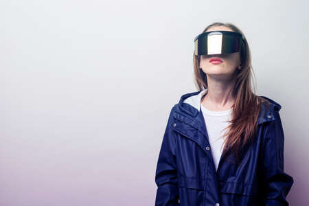 Young girl in virtual reality glasses in a blue jacket on a light background.
