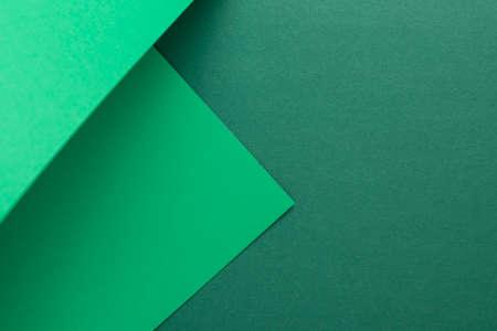 Green cardboard background design folded geometrically. Top view, flat lay.