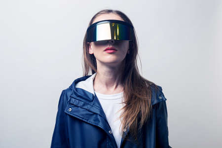 Young woman in virtual reality glasses in a blue jacket on a light background.