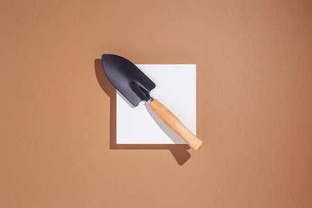 Garden tools small blade lies on a white square podium on a brown background. Top view, flat lay.