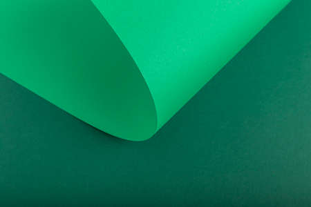 Design background of folded curl from green cardboard. Top view, flat lay.