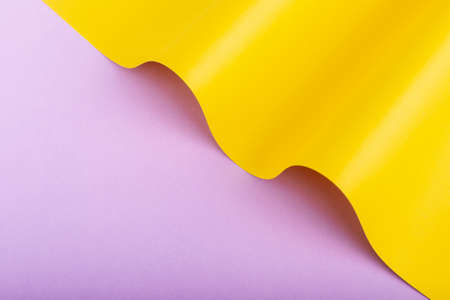 Wave of yellow cardboard on lilac background. Top view, flat lay.