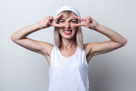 Young blonde woman shows a gesture of two fingers victory and peace on a light background.