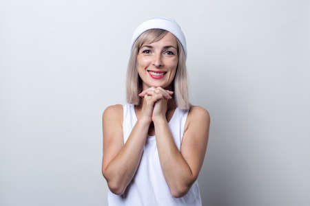 Beautiful smiling young blonde woman in a white hat on a light background. Фото со стока