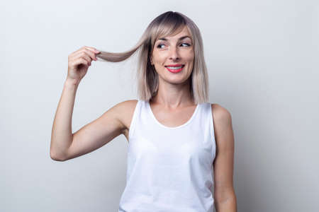 Smiling young blonde woman looking at holding a lock of hair on a light background. Фото со стока
