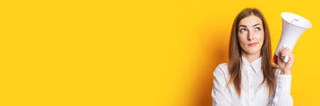 Young woman with a pensive face holds a megaphone in her hands on a yellow background. Hiring concept, help wanted. Banner.