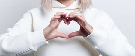 Female hands show a heart gesture on a light background. Banner. Фото со стока