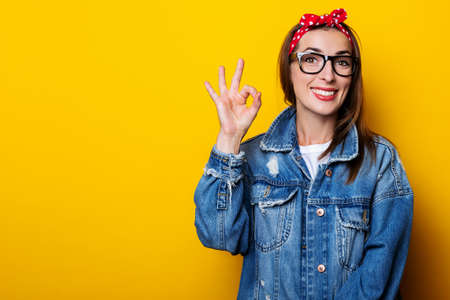 Smiling young woman in hair band, in denim jacket shows ok gesture, okay on yellow background Фото со стока