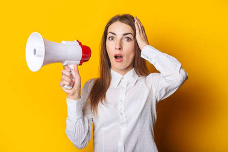 Young woman with a surprised face in a white shirt holds a megaphone in her hands on a yellow background. Hiring concept, help wanted. Banner. Фото со стока