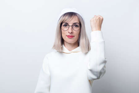 Young woman in a hoodie shows the feminine power on a light background. Фото со стока