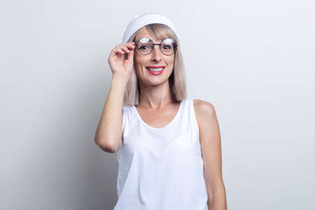 Beautiful smiling young blonde woman with glasses on a light background.