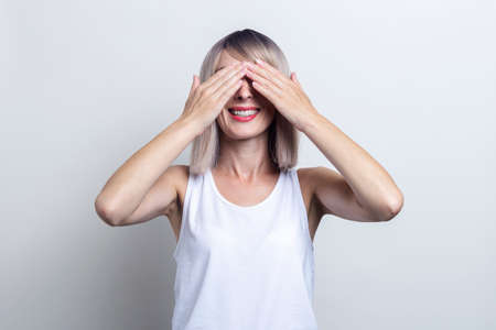 Smiling young blonde woman with her palms closed her eyes on a light background.