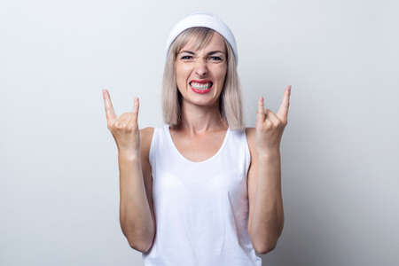 Young blonde woman shows rocker horns on a light background.