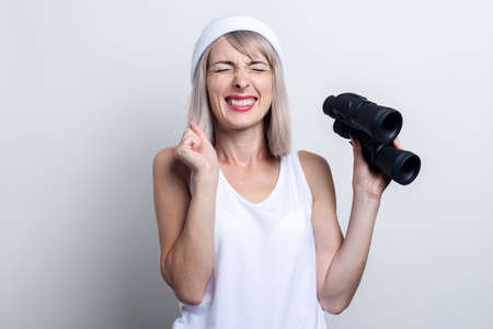 Cheerful young woman with binoculars screwing up her eyes with closed eyes on a light background.