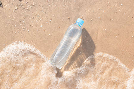 Plastic water bottle on the beach is washed by a wave. Top view, flat lay. Фото со стока
