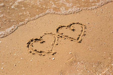 Two hearts drawn on a sandy beach. Top view, flat lay. Фото со стока