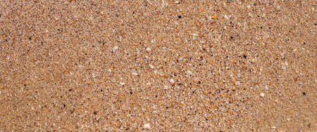 Beach sand texture on a summer day. Top view, flat lay. Banner.