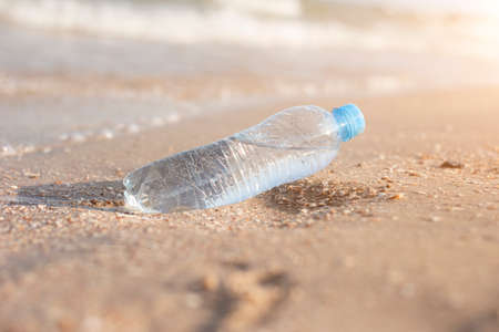 Plastic bottle with water on the background of a sandy beach on a sunny day.