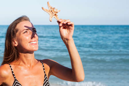 Smiling young woman is covered by a starfish from the sun on the background of the sea.
