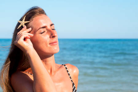 Young woman with closed eyes with a starfish on the background of the sea.