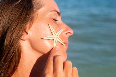Young woman with closed eyes holding a starfish on the cheek against the sea.