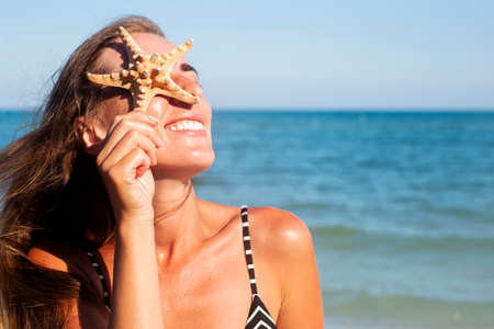 Smiling young woman with starfish closes her eye with starfish on the background of the sea.
