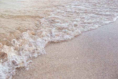 Soft transparent wave of the sea on a sandy beach. Фото со стока