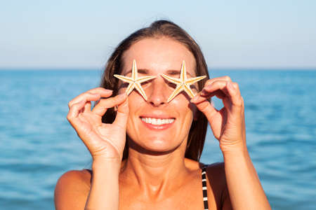 Smiling young woman covering her eyes with starfish on the background of the sea. Фото со стока