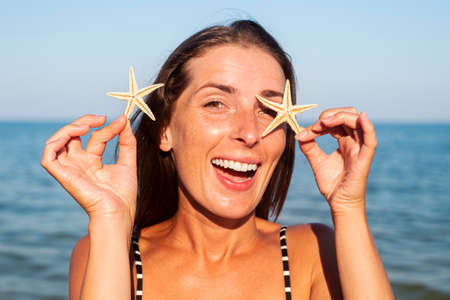 Smiling young woman with starfish on the background of the sea.