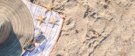 Gold starfishes, hat, glasses on the sandy beach. Top view, flat lay. Banner.