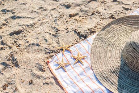 Gold starfish, hat on the sandy beach. Top view, flat lay. Фото со стока